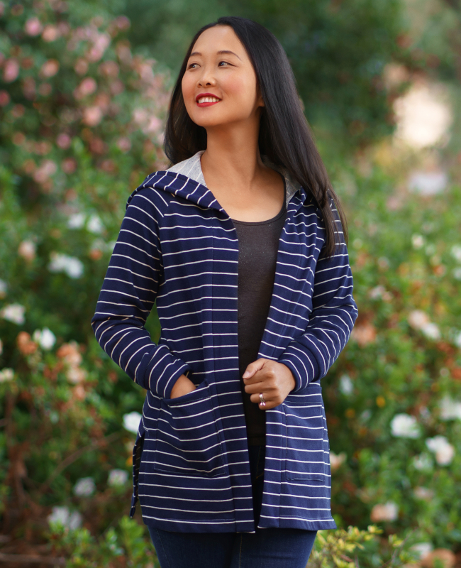 Model wears a long line cardigan with a hood made from blue and white striped jersey